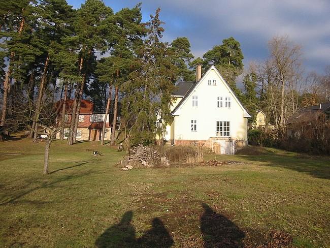 Einfamilienhaus vor der Sanierung: Wiese mit Nachbarhaus links, Haus rechts und Bäumen dazwischen und dahinter