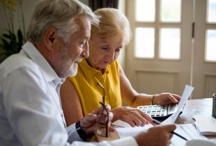 Seniorenpaar sitzt am Tisch und kalkuliert Fördermittel durch