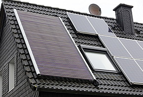 Auf dem Bild ist das Dach eines Hauses mit Solarthermie-Anlage abgebildet.