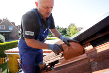 Handwerker verlegt Solar-Dachziegel.