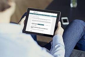 Mann sitzt auf der Couch mit einem Tablet und schaut sich den Fördermittelcheck auf www.co2online.de an.