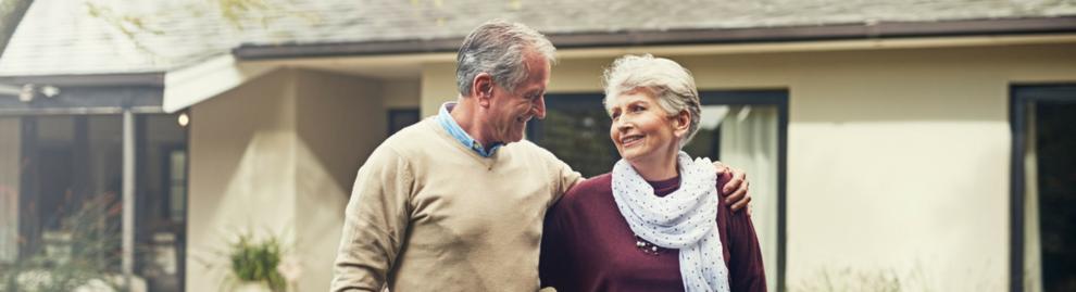 Seniorenpaar vor ihrem Haus