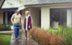 Seniorenpaar mit Gehhilfe vor dem Haus